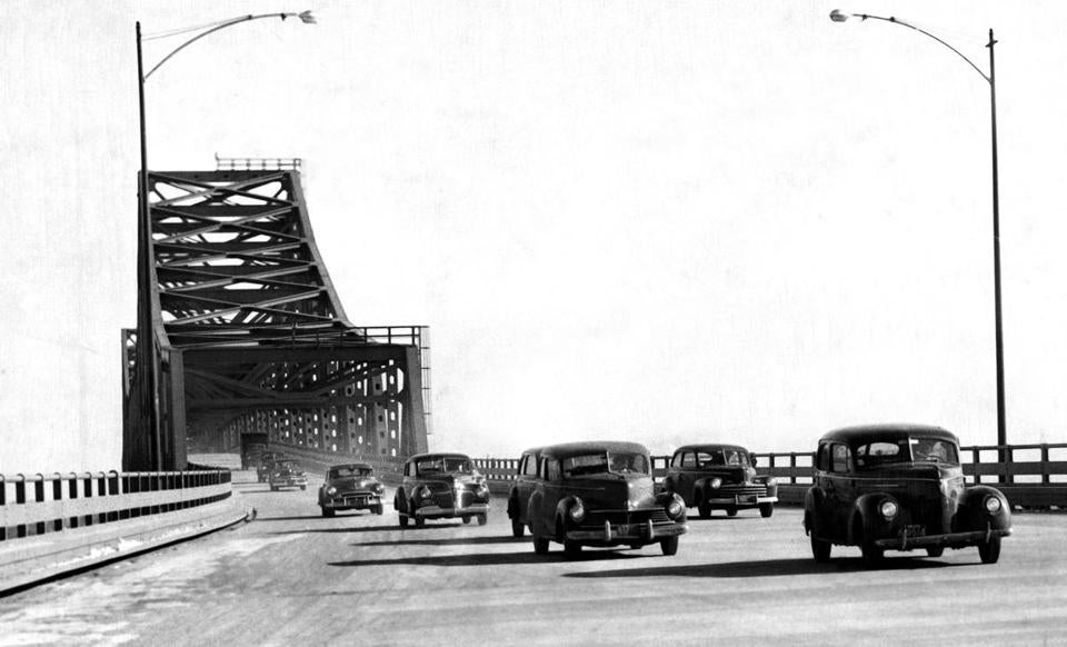 May 4, 1949: The lower half completed, forms went up for concreting the upper pedestals of the Mystic River Bridge. To reach the top of the forms, the company pumped concrete 132 feet straight up. This photograph shows Pier M-3 completed on the Chelsea side. The closeness of the old swing bridge created construction problems while the deep water piers were being built.